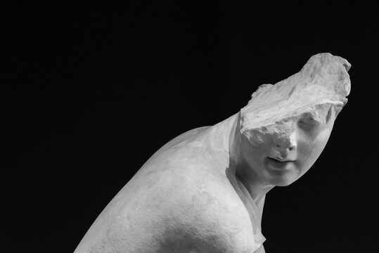 Black and white photo showing ancient roman statue with a broken head
