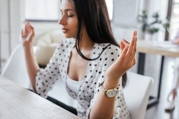 selective focus of beautiful businesswoman with closed eyes meditating in office