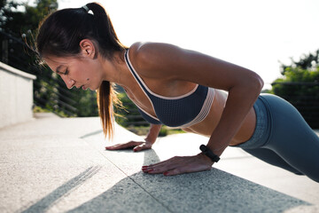 Young woman doing push ups outside