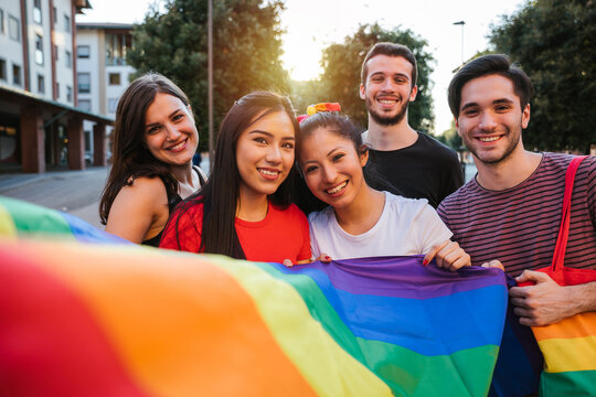 Portrait group of young people demonstration for rights at the gay pride in the city - Millennial holding a flag colorful - Supporters of the LGBT community - Concept shooting of equality social