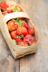 Ripe juicy strawberries in vintage basket. Selective focus. Shallow depth of field.