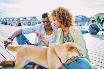 Positive hipster african american friends dressed in casual wear resting with dog in urban setting...