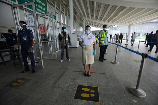 A health worker is seen with an infra-red laser thermometer at the Nnamdi Azikiwe International airport during preparation ahead of the reopening of the airport for domestic flight operations in Abuja
