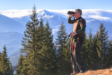 Man who is studying tourist route in the mountains