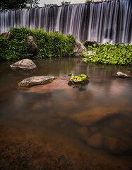 Beautiful waterfall from water dam long exposure shot with calm water surface foreground