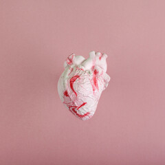 Anatomical human heart model on pink background.