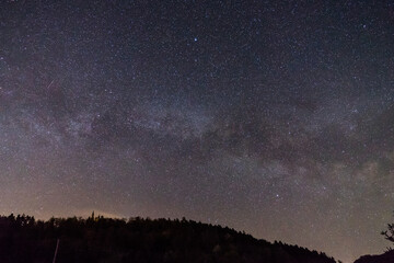 Germany, Moving star field of milky way galaxy core over swabian alb forest tree silhouette and famous ancient castle teck on top of a hill at night
