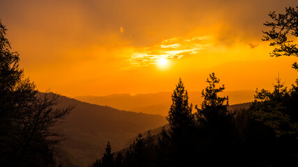 Germany, Dramatic red sky sunset mood over endless silhouette of black forest nature landscape with smooth moving clouds