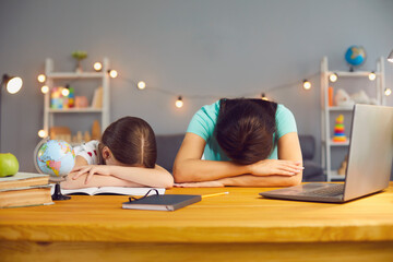 Little girl with her mother lying on table near laptop computer, exhausted from online home...