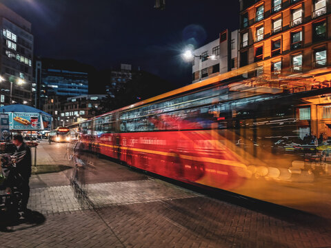 Blurred Motion Of Bus Amidst Illuminated Buildings In City At Night