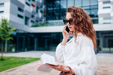 Young sylish businesswoman talking on phone by business center looking at notes