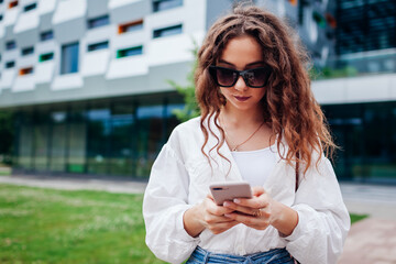 Young student using smartphone outside university. Girl searching online in internet typing message