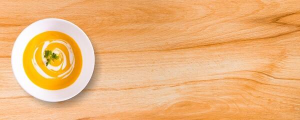 Tigela tipo Bowl branco com creme de cenoura sobre a madeira natural bege