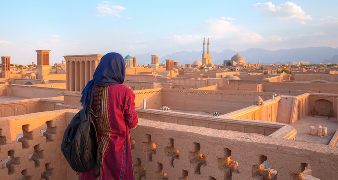 Iranian girl in traditional clothes take a photo - Historic City of Yazd with famous wind towers - Yazd, Iran