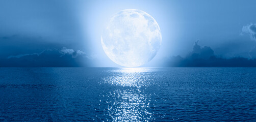 Wall Mural - Night sky with Blue moon in the clouds on the fore ground calm blue sea