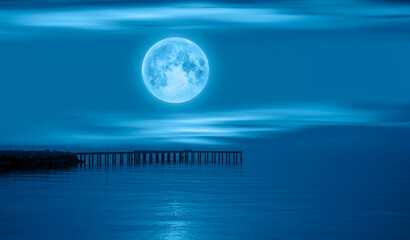Wall Mural - Night sky with full moon in the clouds with pier