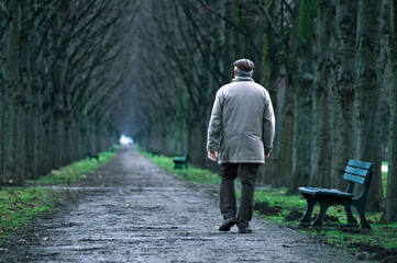 Fototapeta Rear View Of Old Man Walking On Footpath obraz