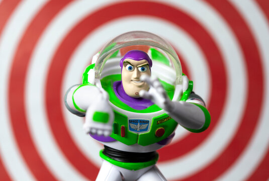 NEW YORK USA - JULY 7 2019: Buzz Lightyear in an action pose from the Toy Story movie franchise with red ring background illustrating his laser beam feature - Disney action figure