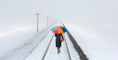 Woman in blackclothes with multicolored umbrella is walking on the railroad tracks - Snow covered railroad tracks