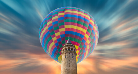 Colorful hot air balloon flying over Galata tower at amazing sunset - Istanbul, Turkey