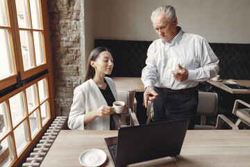 Senior with a young assistant. Businessman working in the cafe. Man in a white shirt. Young woman...