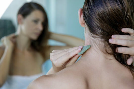Young woman is doing Gua Sha facial massage in bathroom in front of the mirror. Gua Sha jade stone at home treatment.