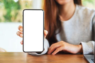 Mockup image of a beautiful woman holding and showing a mobile phone with blank white screen