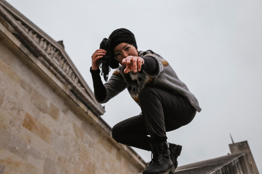 Low Angle Portrait Of Woman Gesturing While Crouching In City Against Sky