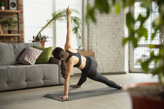 Vitality. Sporty arabian, muslim beautiful young woman taking professional yoga lessons online and practice at home. Concept of healthy lifestyle, wellness, wellbeing, hobby. Flexible and motivated.