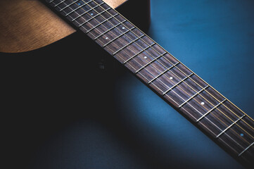 Acoustic guitar, music instrument resting against a dark black background with copy space, Close-up of wooden classic guitar Wall mural