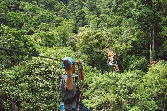 Woman Ziplining In Forest