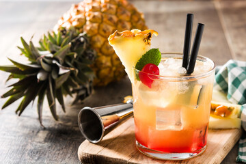Cold mai tai cocktail with pineapple and cherry on wooden table.