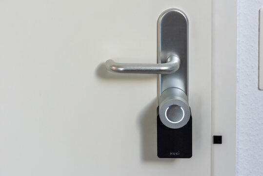 Ostfildern, Germany - June 22, 2020: Entrance door being equipped with a Nuki Smartlock and open door detection . Concept of using smart electronic locks with keyless access.