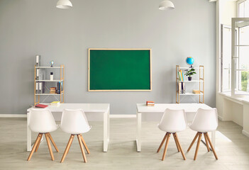 Empty school classroom interior with desks and chairs, space for text on chalkboard. Modern schoolroom with furniture
