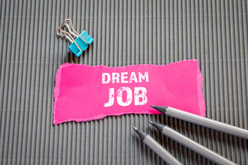 DREAM JOB. Career, education and job interview concept. Text on torn, colored paper
