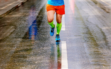 Wall Mural - legs runner in compression socks run on wet road after rain