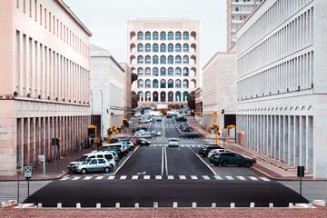 Fotomurales - Vehicles On Road Amidst Buildings In City