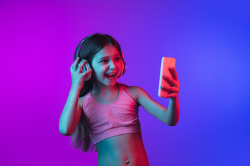 Taking selfie with phone in headphones. Little girl's portrait on gradient pink-blue background in neon. Concept of human emotions, facial expression, modern gadgets and tech, sales, ad. Copyspace.