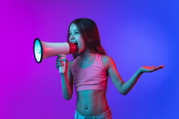 Shouting with megaphone. Little girl's portrait isolated on gradient pink-blue studio background in...