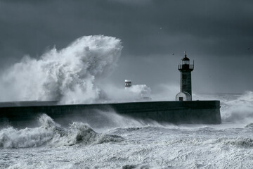 Stormy waves over piers and lighthouse