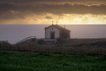 Chapel by the sea at orange sunset