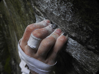 Rock climbers fingers holding on to a crimp on rock, with chalk and tape on hand.