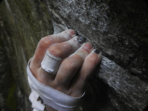 Rock climbers fingers holding on to a crimp on rock, with chalk and tape on hand. High Resolution