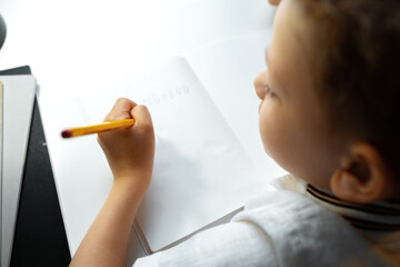 Little boy writing something in his notebook
