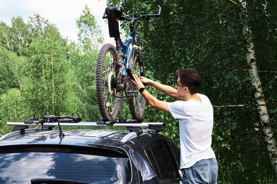 Man is mounting bikes on the roof of a car on a summer sunny day for transportation