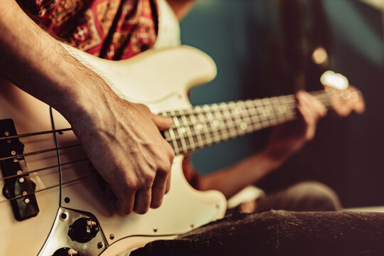 Close up of male hand playing electric guitar in the dark