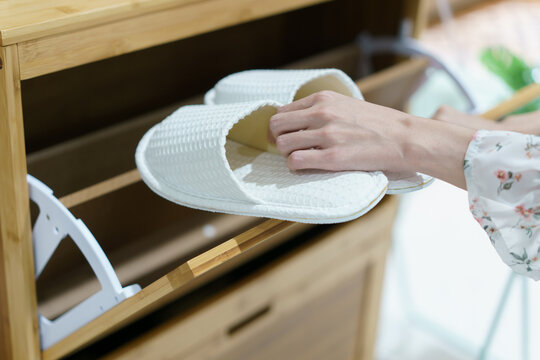 Woman opening wooden shoes storage cabinet for keep her shoes.
