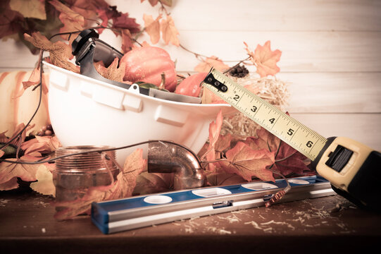 Happy Thanksgiving with construction tools, maple leaves and pumpkin on wood background. Autumn composition with copy space. Plumber Thanksgiving.