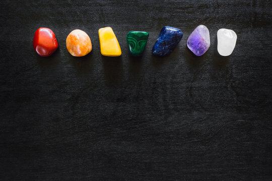 Top Aligned Rainbow Chakra Stones on Black Background