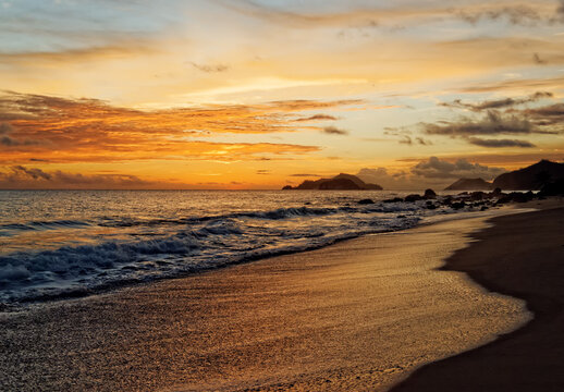 romantic sunset on beach at seychelles island glittering surf and ocean water